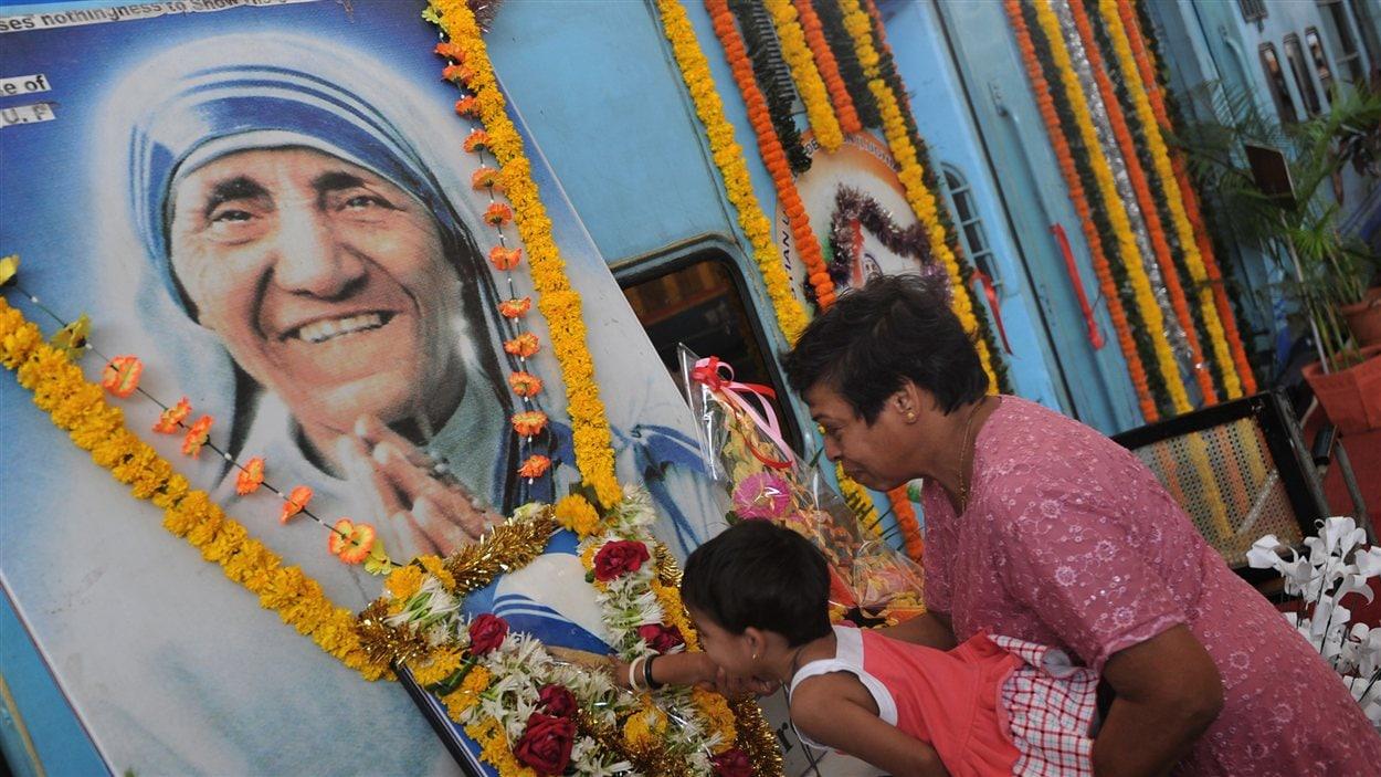 Des Indiens se recueillent devant une image de Mère Teresa