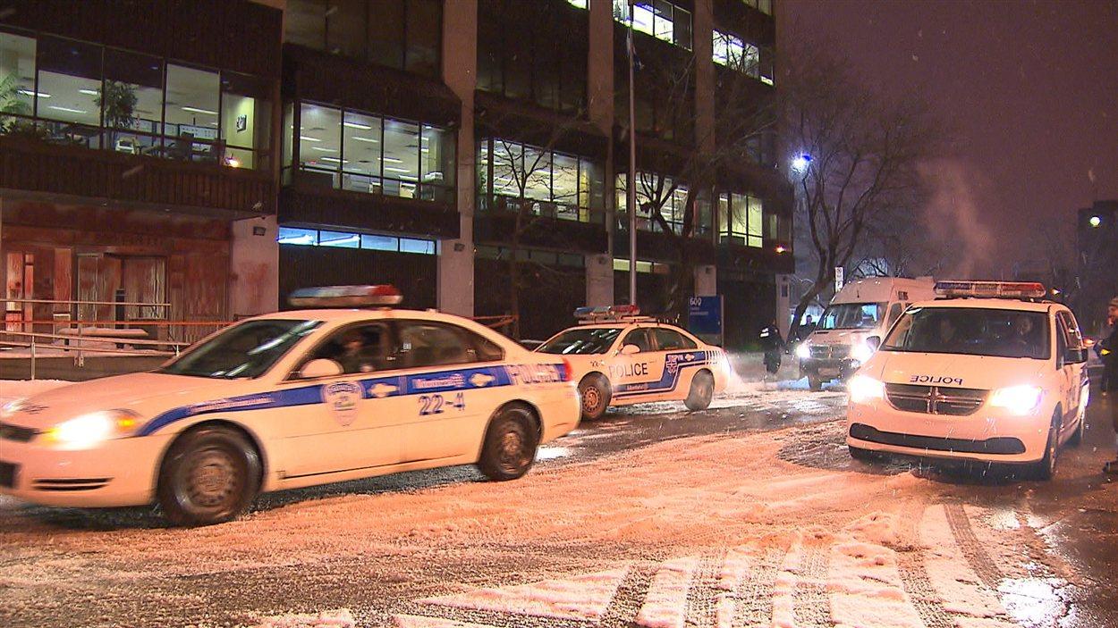 Des voitures de police arrivent devant les locaux du ministère de l'Éducation, à Montréal, où l'entrée a été aspergée de peinture rouge.