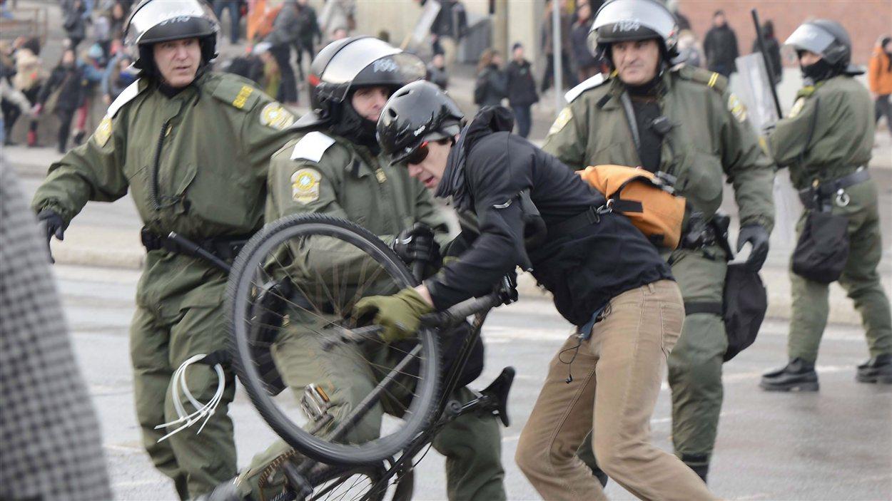 Des policiers de la SQ chargent un manifestant.