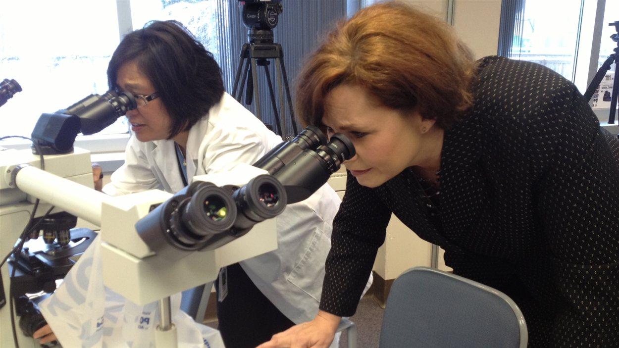 La ministre de la Santé du Manitoba Theresa Oswald (droite) regarde dans un microscope lors de l'annonce d'un nouvel appareil de diagnostic pour le cancer du sein à l'Hôpital général de Saint-Boniface, le 5 mars 2013.