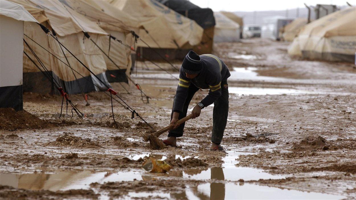 Un réfugié syrien stabilise une tente dans le camp de Zaatari, à la frontière entre la Syrie et la Jordanie.