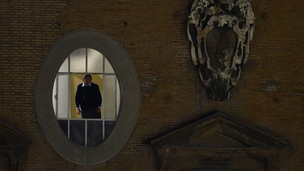 Une religieuse se tient à sa fenêtre donnant sur la place Saint-Pierre alors que la fumée blanche vient de s'échapper de la cheminée de la chapelle Sixtine, le 13 mars 2013