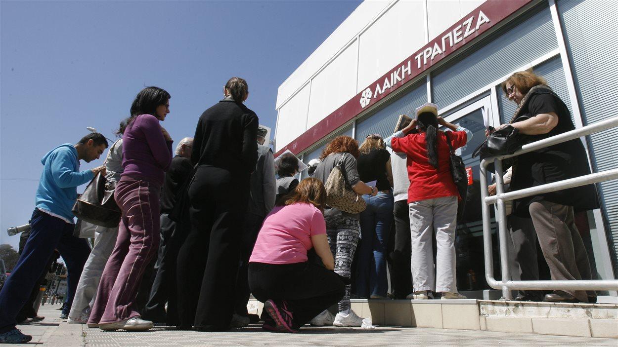 Des clients attendaient fébrilement l'ouverture de cette succursale bancaire, à Nicosie.