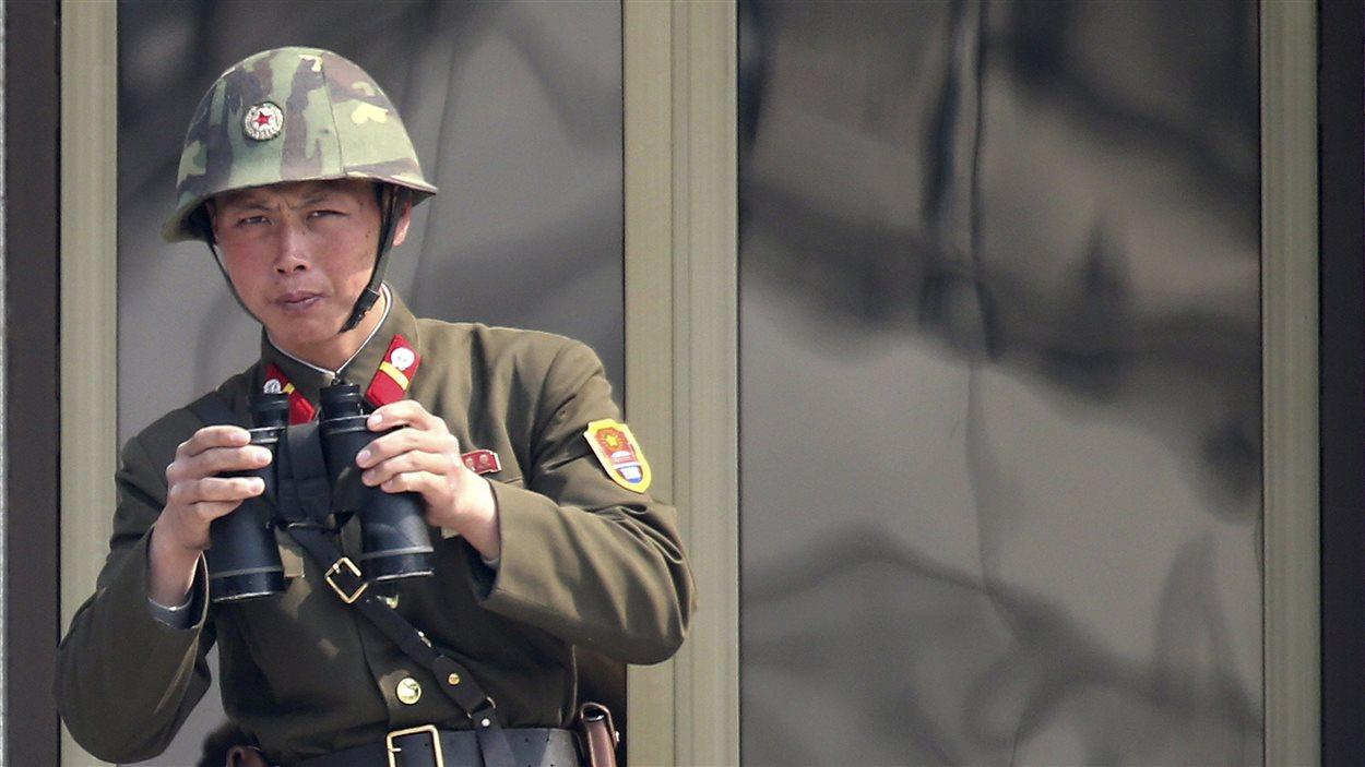 Un soldat nord-coréen regardant la Corée du Sud dans la zone démilitarisée