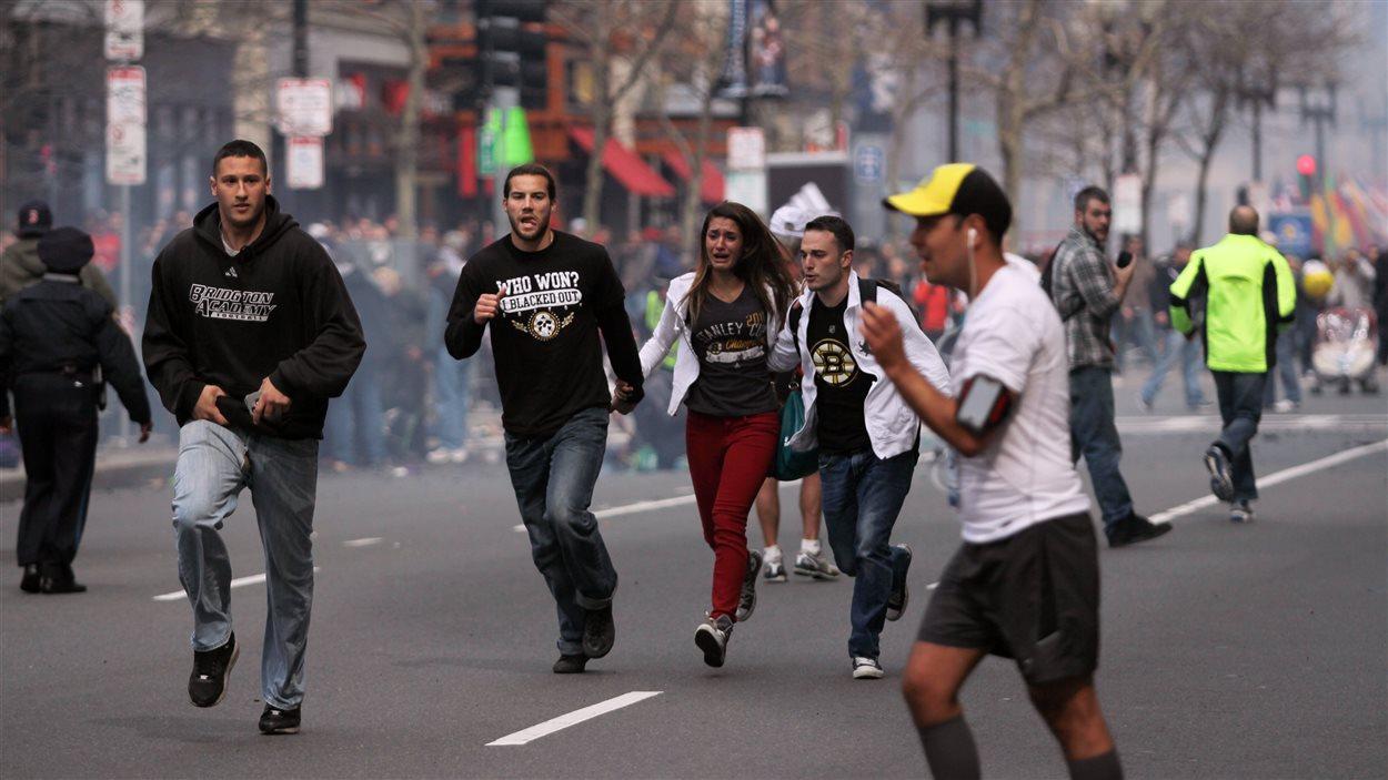 Des gens s'enfuient du site de l'explosion au marathon de Boston.