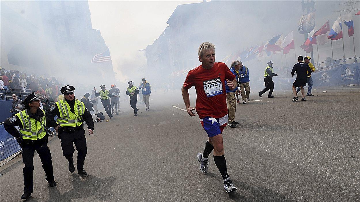 Des coureurs et des policiers courent pour fuire une explosion pendant le marathon de Boston.