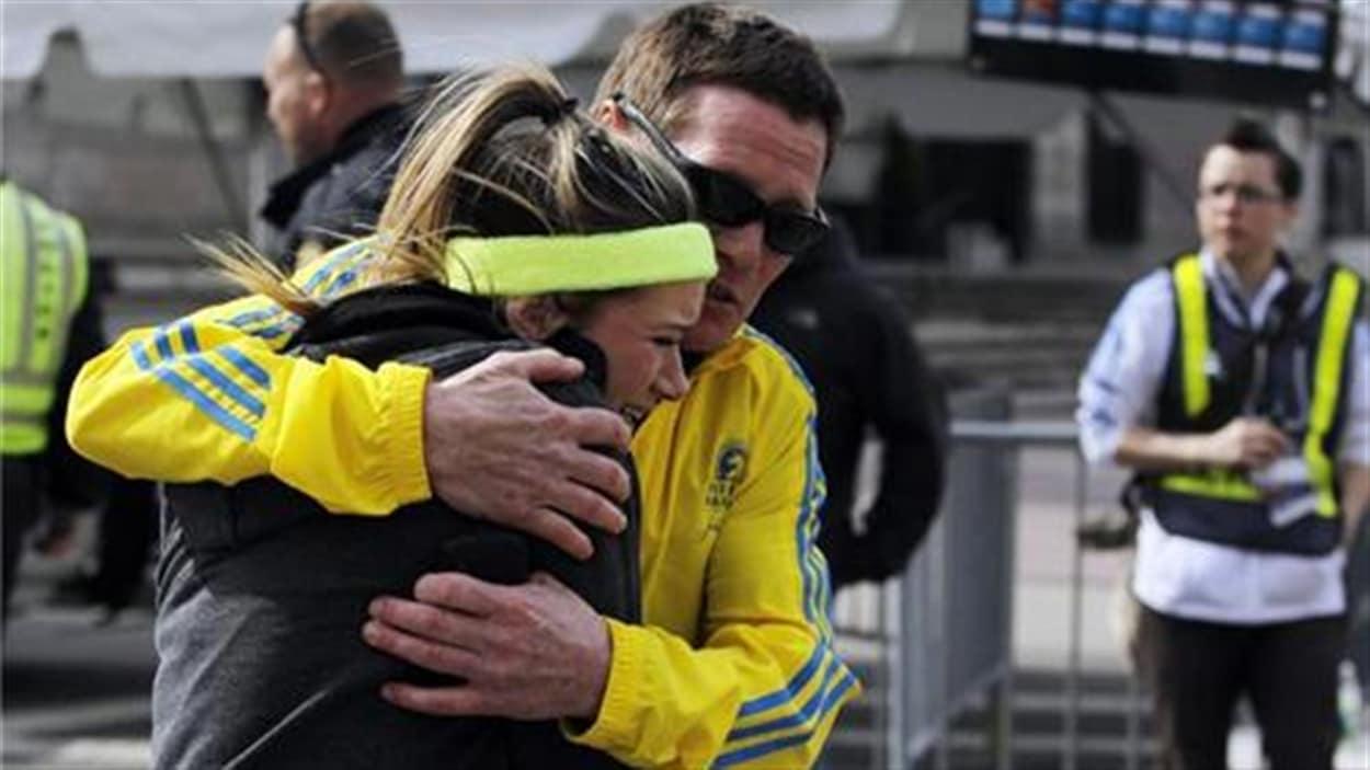 Une participante au Marathon de Boston se fait consoler après l'explosion.