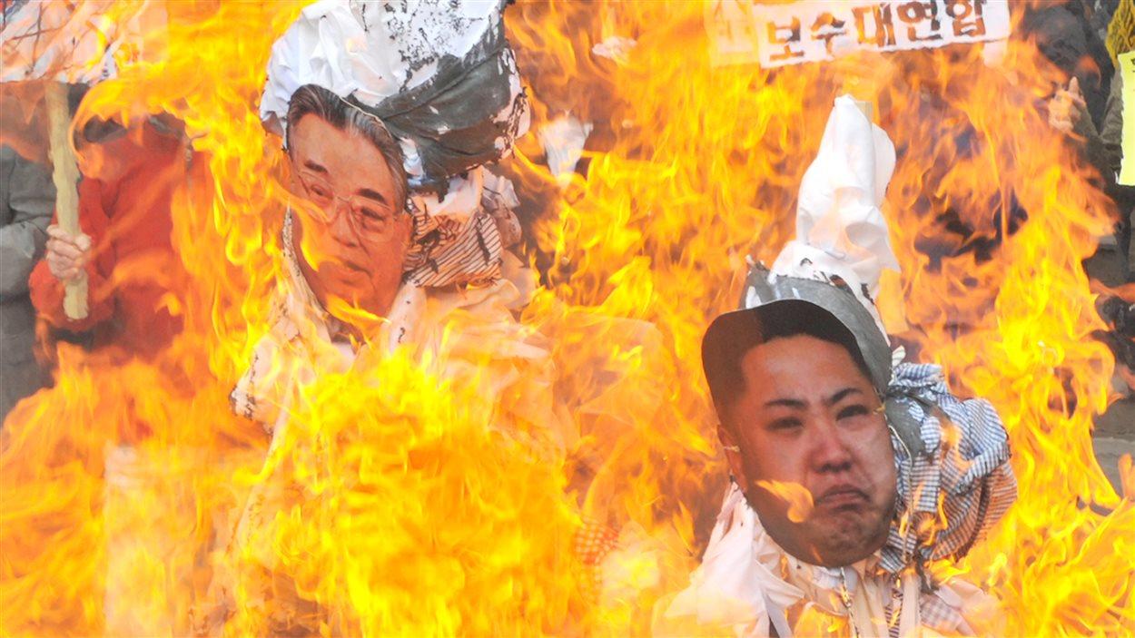 Des manifestants brûlent des portraits des dirigeants nord-coréens, à Séoul.