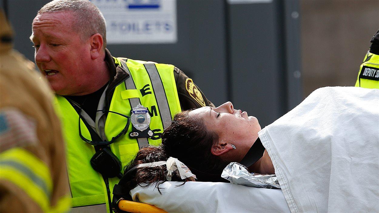 Une femme blessée par une des explosions est emmenée par un ambulancier.