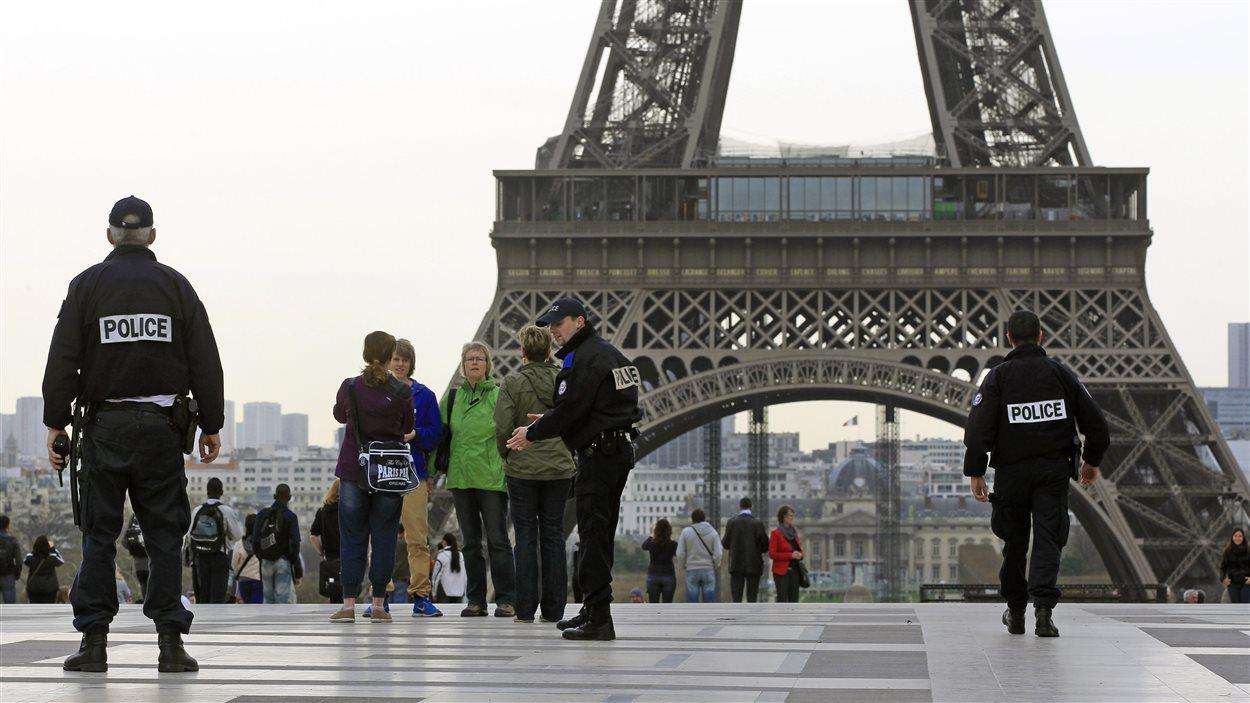 Des polciers montent la garde aux abords de la tour Eiffel, à Paris.