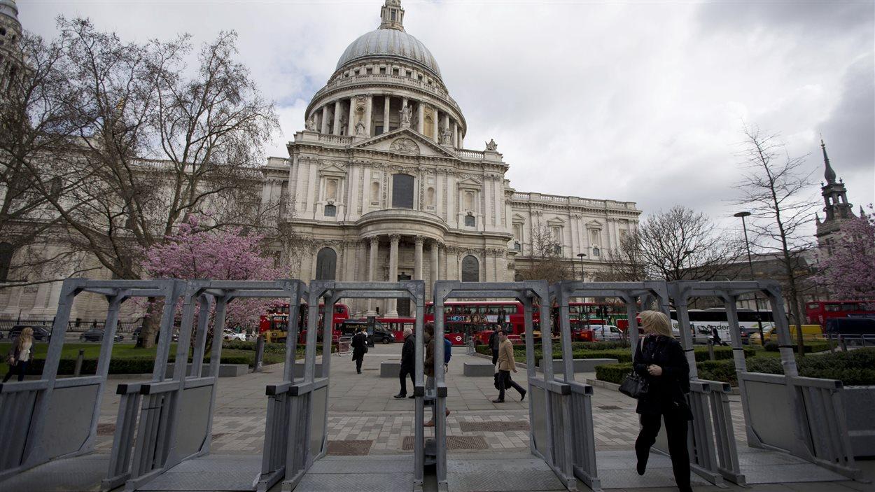Une femme traverse des guérites de sécurité placées devant la cathédrale St-Paul de Londres, où doivent être célébrées les funérailles de l'ex-première ministre Margaret Thatcher.