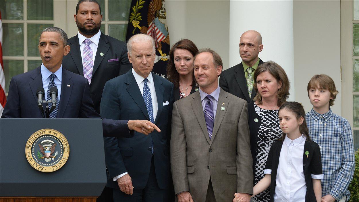 Le président Obama était notamment entouré du vice-président Joe Biden et de parents de victimes de la tuerie de l'école Sandy Hook à Newtown au Connecticut.