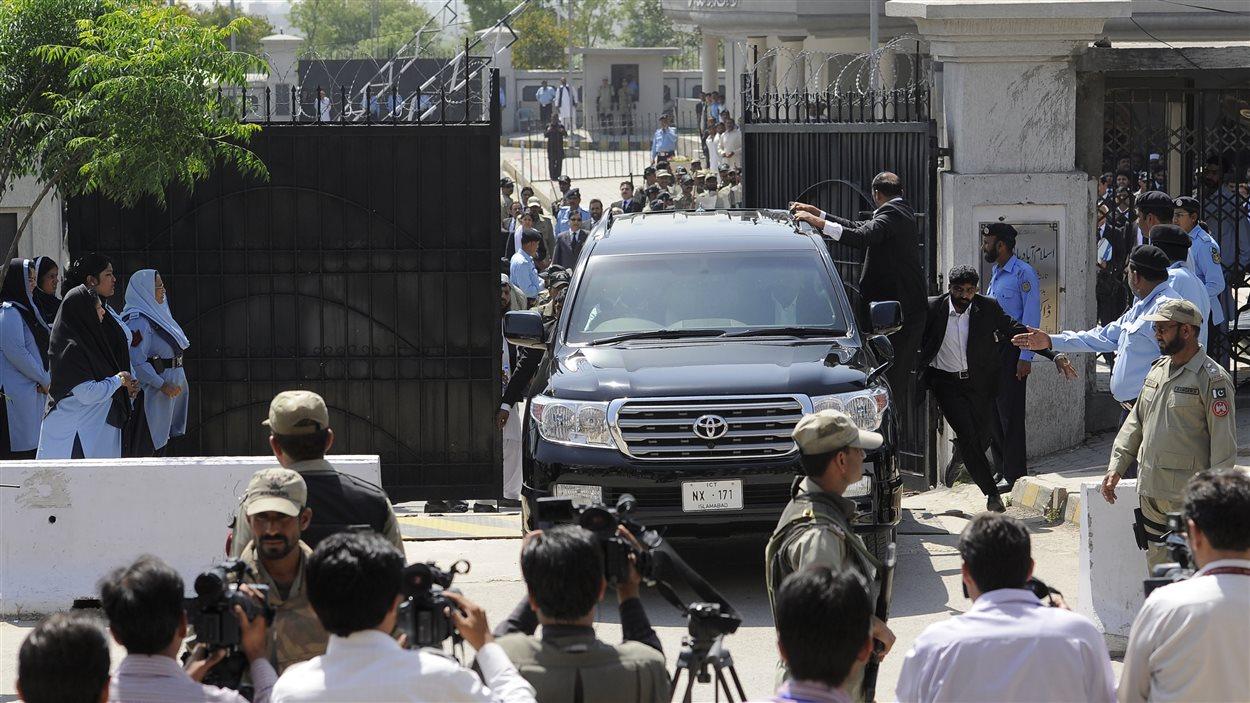 L'ancien président pakistanais Pervez Musharraf et ses gardes du corps prennent la fuite à bord d'une voiture noire.