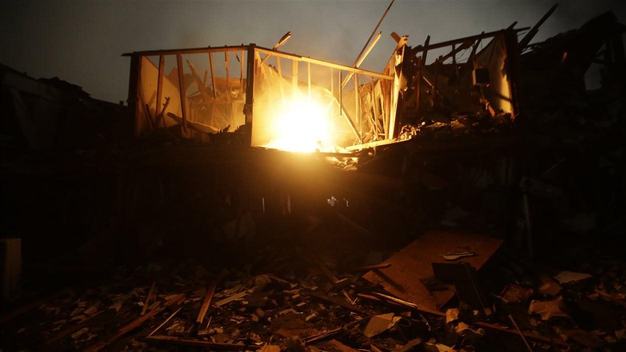 Un feu brûle dans les décombres d'un complexe d'appartements de West.