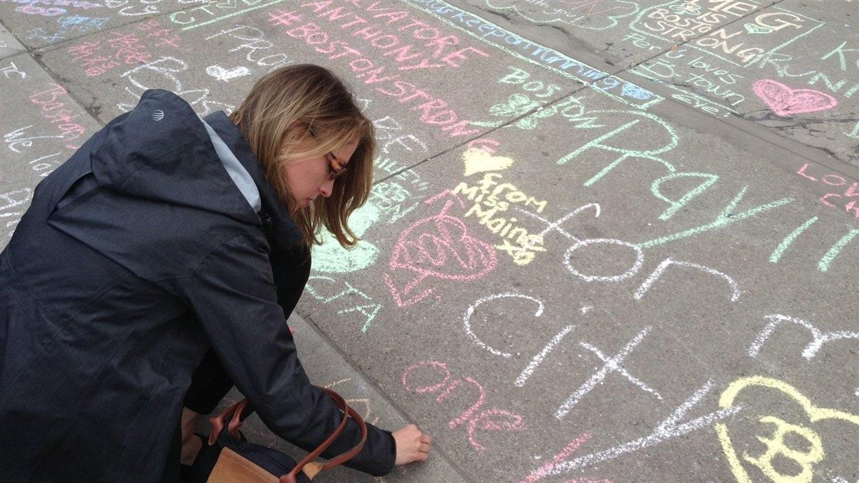 À Boston, une passante ajoute un message à la craie sur le sol.
