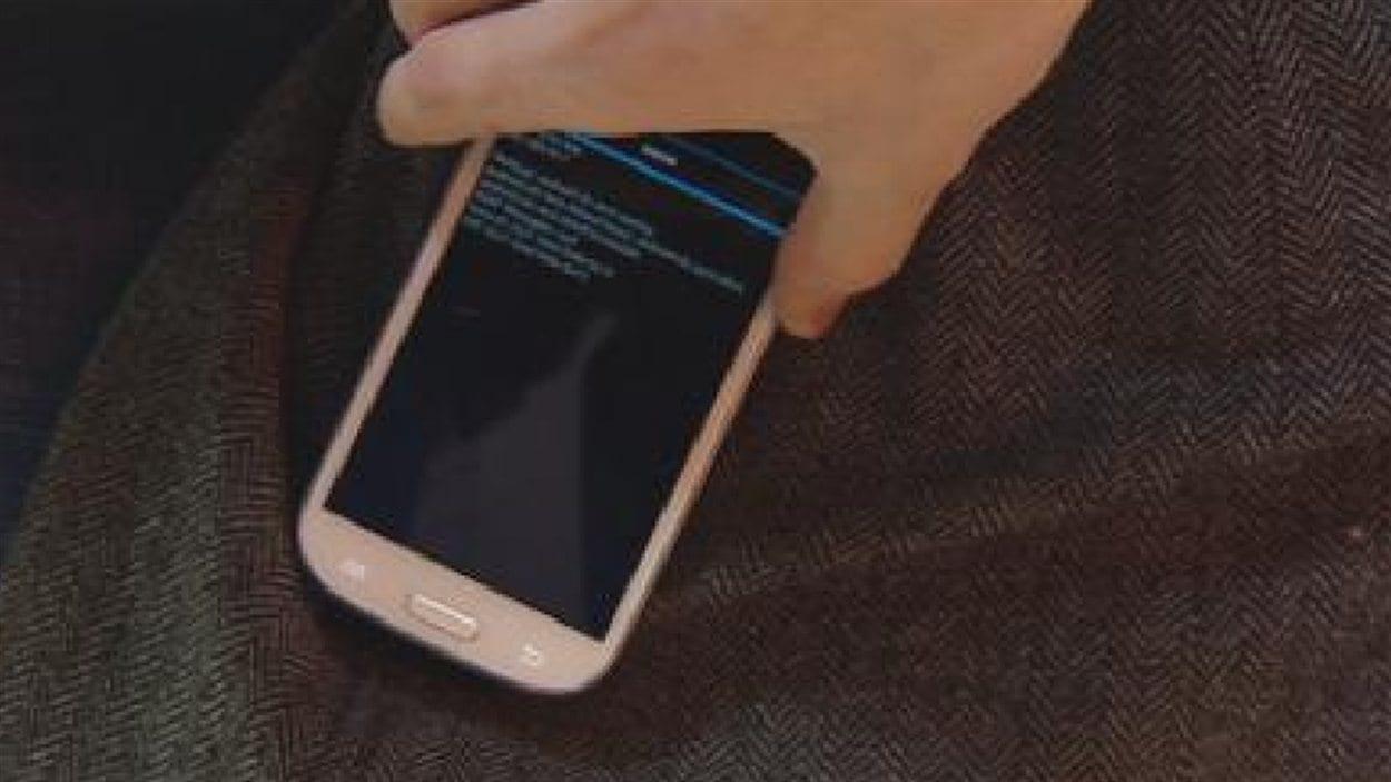 Une application sur un téléphone intelligent déchiffre les informations d'une carte de crédit insérée dans la poche d'un manteau.