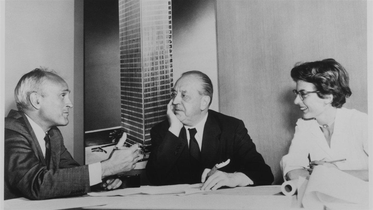 Philip Johnson, Mies van der Rohe et Phyllis Lambert, avec en arrière-plan, une imagede  la maquette de l'édifice Seagram, New York, 1955. Épreuve argentique à la gélatine,  17,78×22,86 cm. Photographe inconnu.