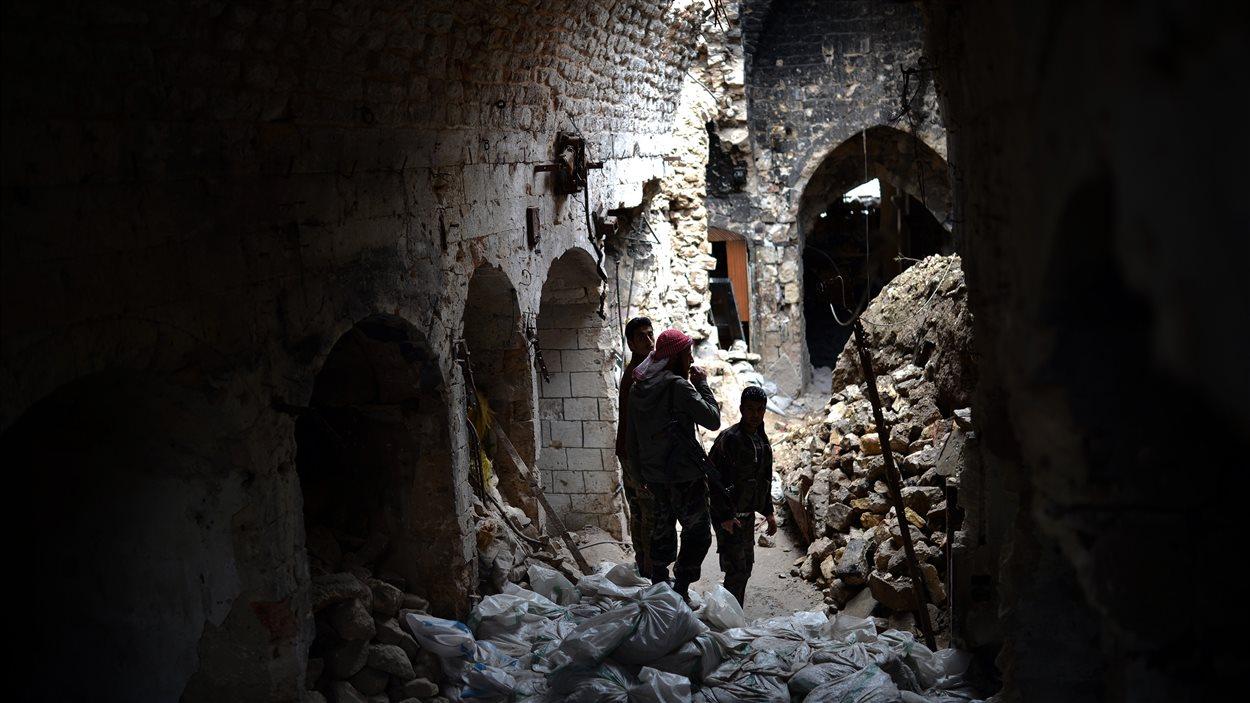 Des rebelles syriens dans les décombres de la mosquée de la ville d'Alep, le 16 avril 2013