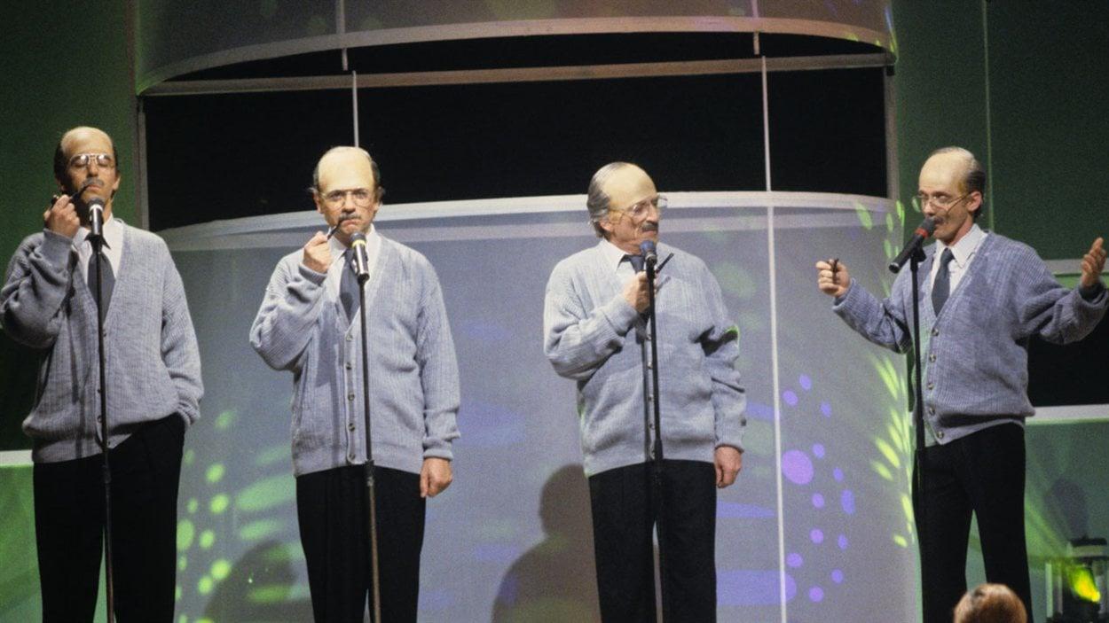 Sur une scène, les humoristes Alain Dumas, Jean-Guy Moreau, Jean Lapointe et Pierre Verville, imitant tous les quatre le chanteur Fernand Gignac en 1991.