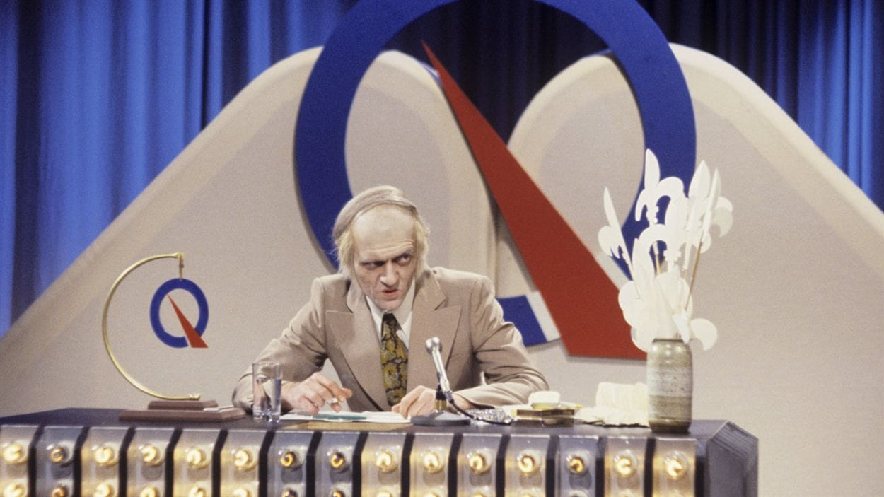 """Sketch """"Jeu-questionnaire Le PQ"""" : Dans un studio de télévision, l'animateur René Lévesque (Jean-Guy Moreau) est assis à un pupitre lors du Bye bye en 1980."""