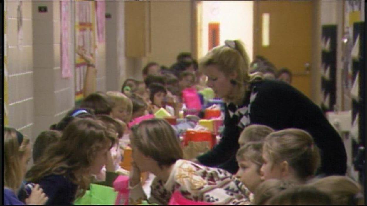 Des élèves dînent dans le corridor à l'École Taché en 1991, faute d'espace dans l'établissement francophone du quartier Saint-Boniface de Winnipeg.
