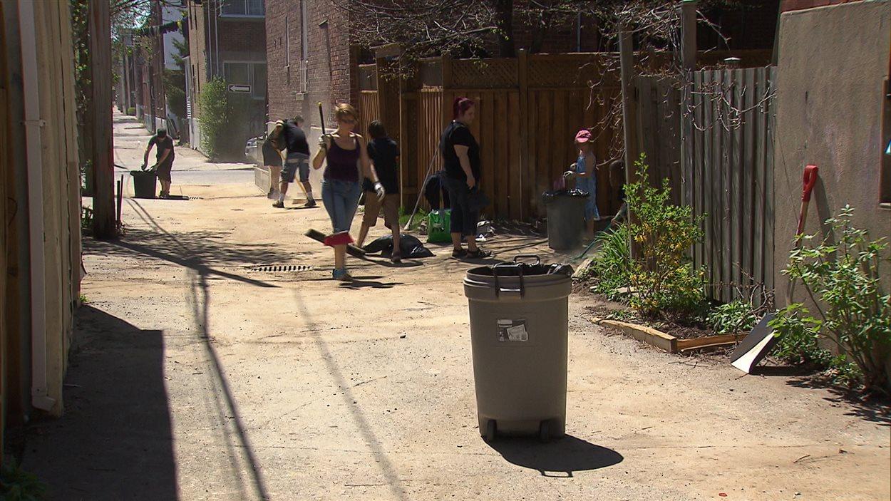 Des Montréalais nettoient leur ruelle.