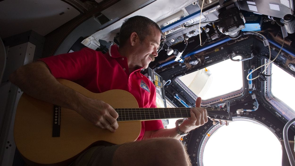 Chris Hadfield joue de la guitare dans la coupole d'observation de la SSI.