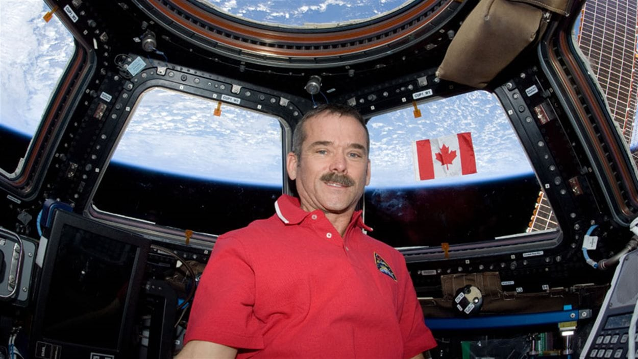 Chris Hadfield et le drapeau canadien, dans la coupole de la station.