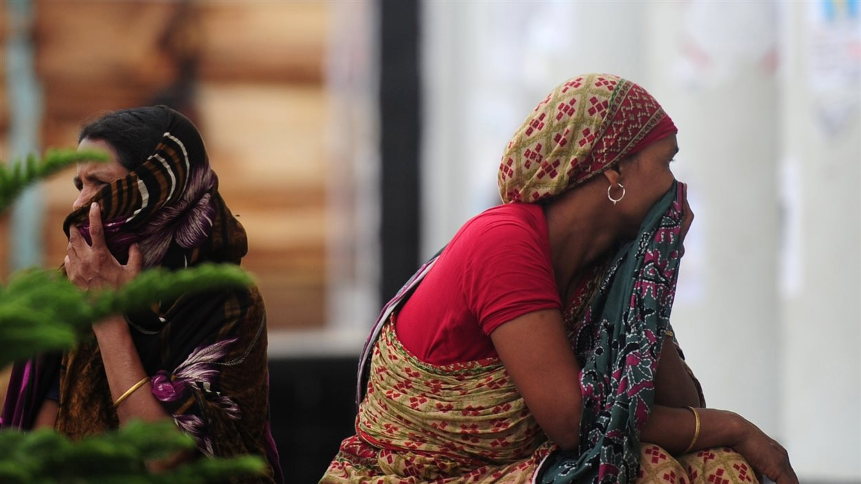 Une famille bangladaise attend que le corps d'un des leurs soit retiré des décombres de l'effondrement, le 7 mai 2013