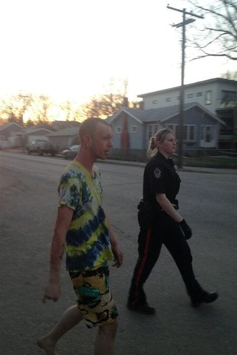 Un homme blessé suit une policière en direction de sa voiture, après une explosion dans une maison de la 13e Avenue à Regina, le 6 mai 2013.