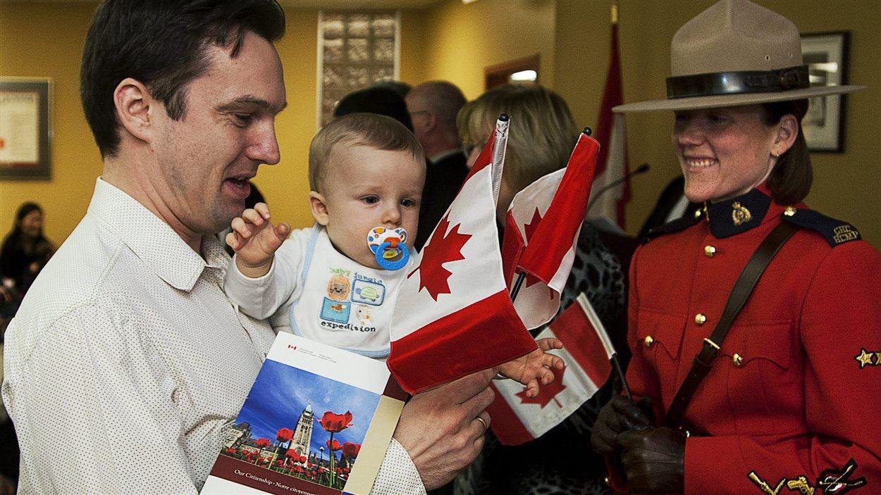 La constable Meredith Darrah regarde Michael Kopec, originaire de la Slovaquie, qui prend part avec son fils Max à une cérémonie de citoyenneté, à Halifax, le 15 février 2011.