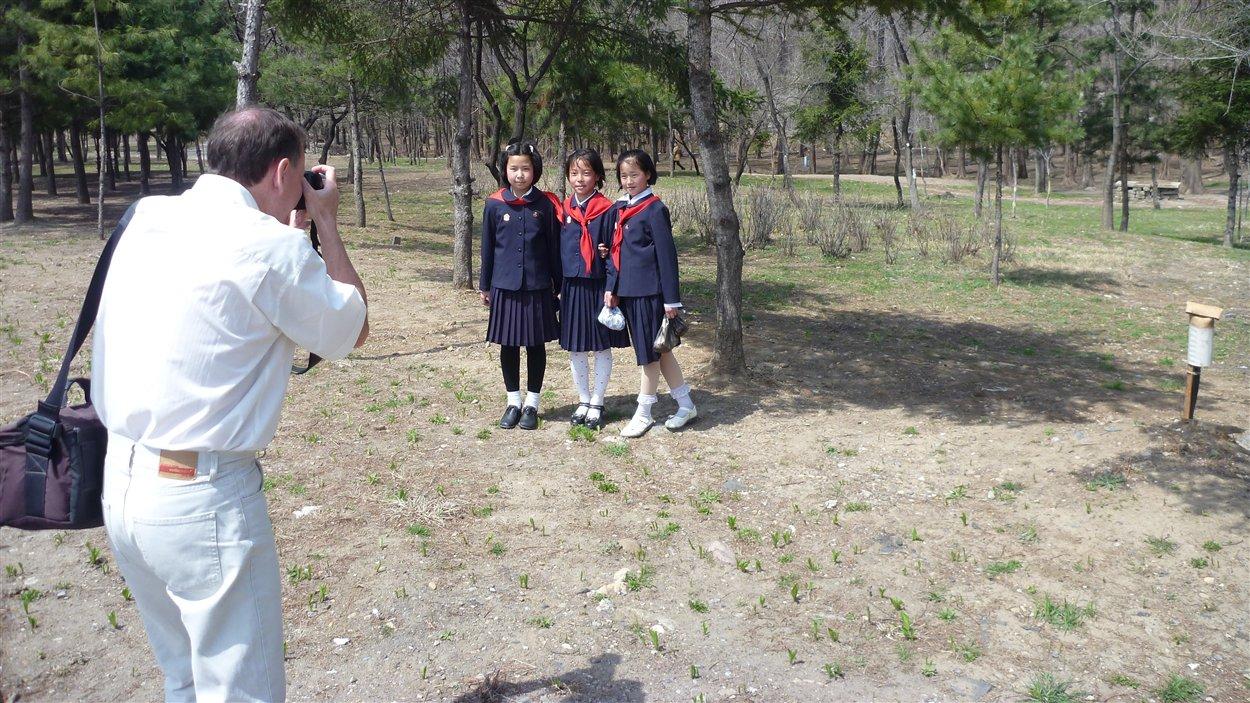 Un touriste français prend en photo les jeunes élèves en uniforme qui se rendent à l'école.