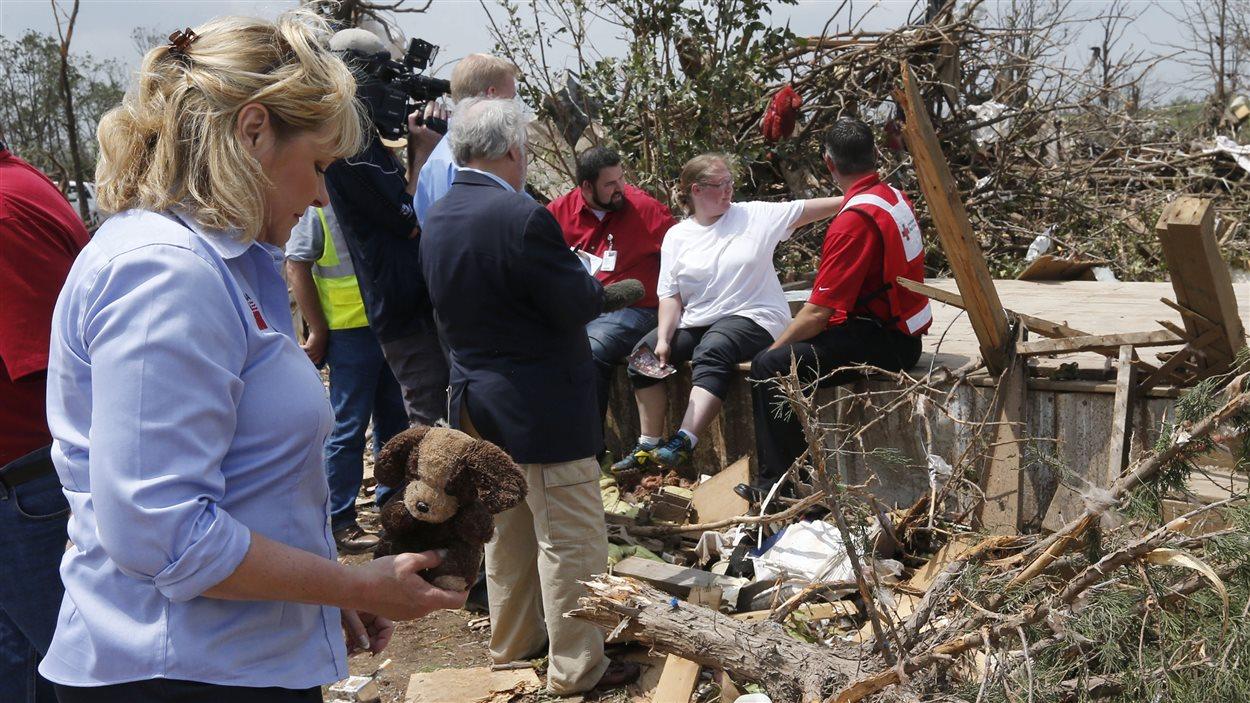 Une femme récupère un chien en peluche dans les débris de sa maison.