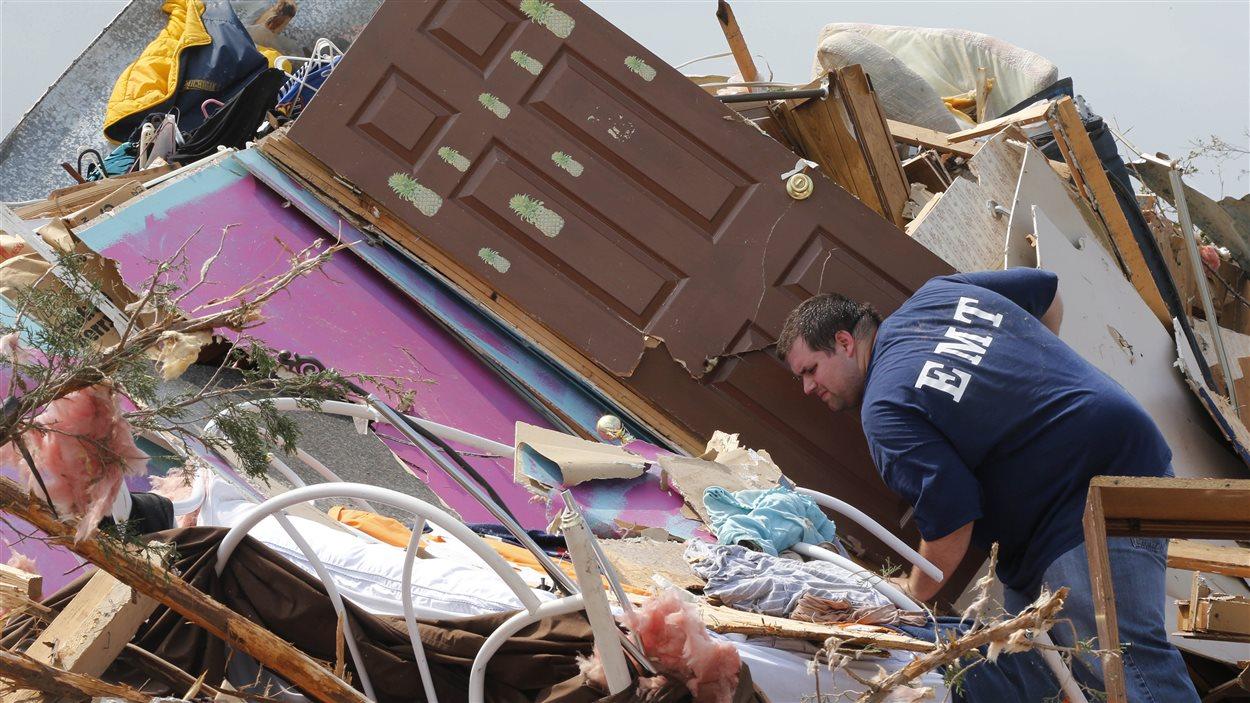 Un homme effectue des recherches dans les décombres de sa maison.
