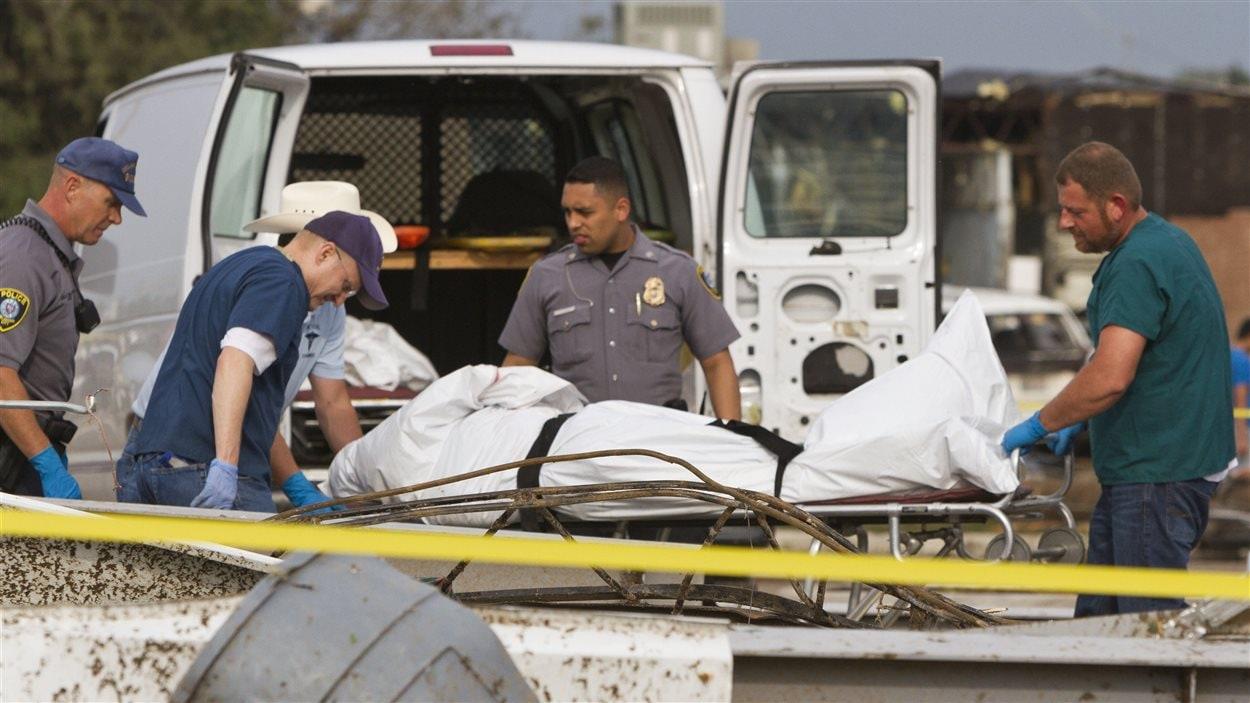 Le corps d'une victime de la tornade est récupéré par les secouristes.