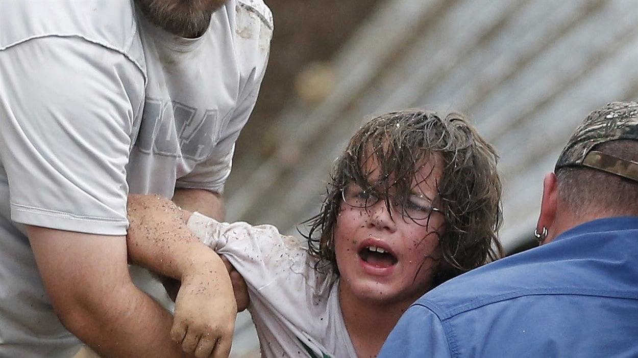 Un enfant appelle son père après avoir été sorti des débris de l'école primaire Plazza Towers à Moore.