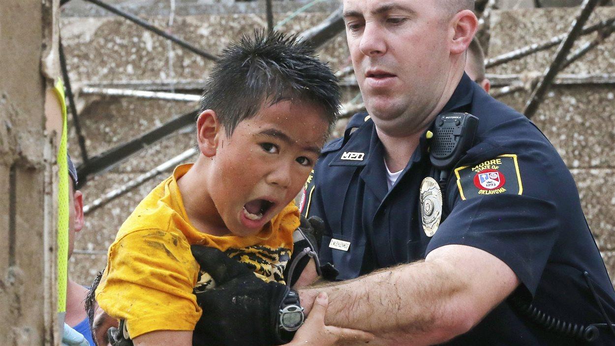 Un enfant secouru par un policier de Moore