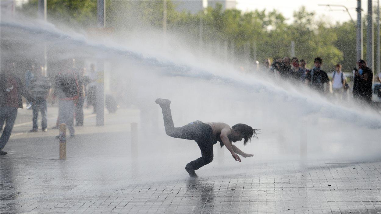 Un manifestant renversé par le jet d'un canon à eau.