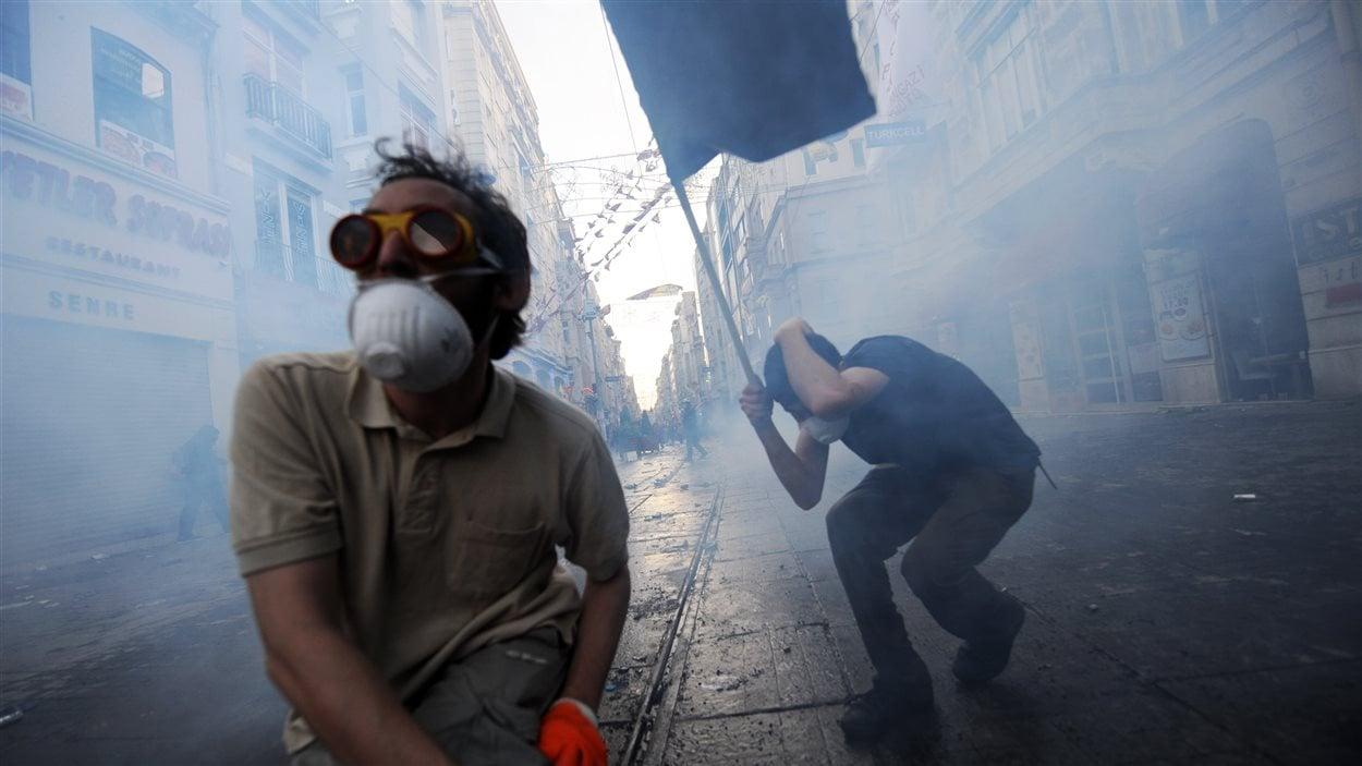 Des manifestants tentent d'éviter les gaz lacrymogènes.