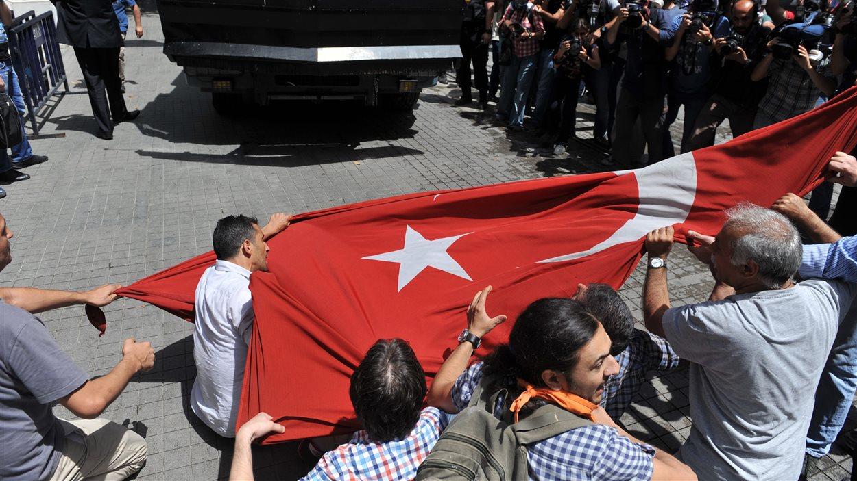 Des manifestants brandissent le drapeau turc face à un camion anti-émeute de la police.