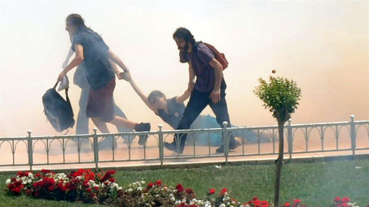 Des manifestants évacuent une blessée.