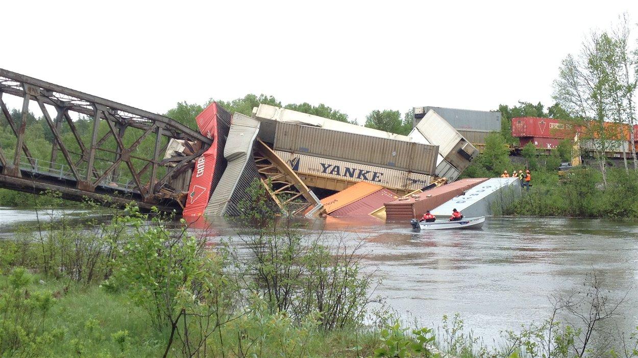 Des wagons du train de marchandise sont tombés dans la rivière lorsque le pont s'est effondré.
