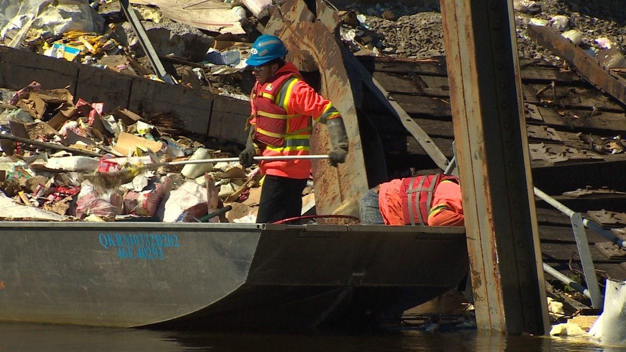 En bateau, des travailleurs du Canadien Pacifique s'affairent à récupérer les débris sur la rivière Wanapitei.
