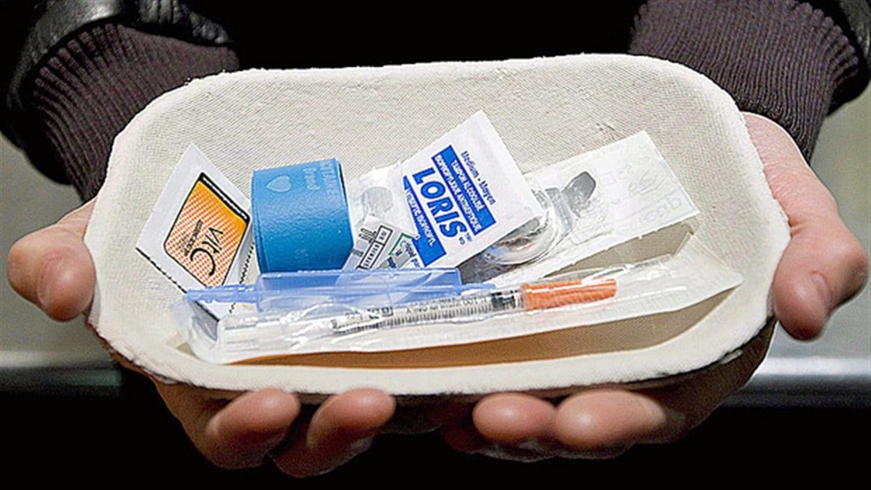 Un homme tient un nécessaire à injection supervisée de drogue.