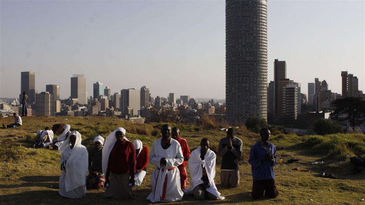 Inquiétés par le ton alarmant du communiqué de la présidence, des Sud-Africains prient pour Nelson Mandela à Johannesburg.