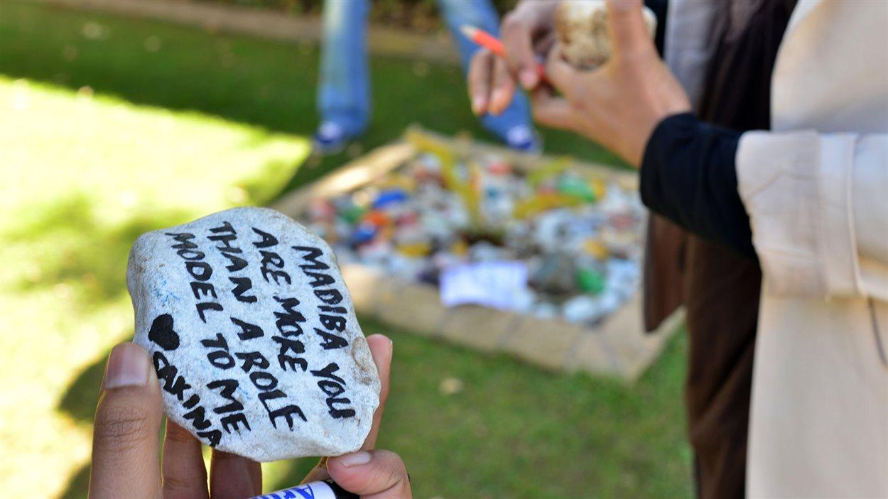 Des dizaines de personnes se sont réunies devant la maison de Nelson Mandela à Houghton, à Johannesbourg, en signe de compassion. Ici, on peut lire : « Madiba, vous êtes plus qu'un modèle pour moi - Sakima ».
