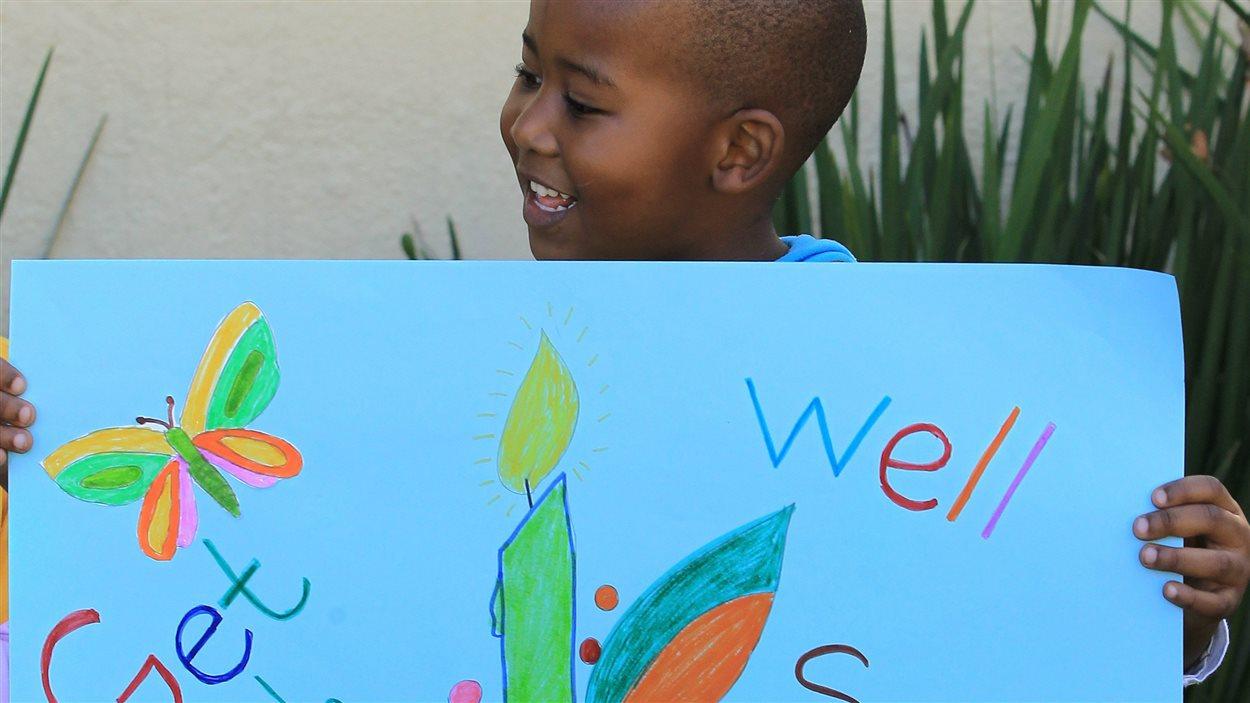 Un jeune garçon du centre communautaire d'Othandwen tient une affiche disant : « Rétablis-toi vite, Madiba ».