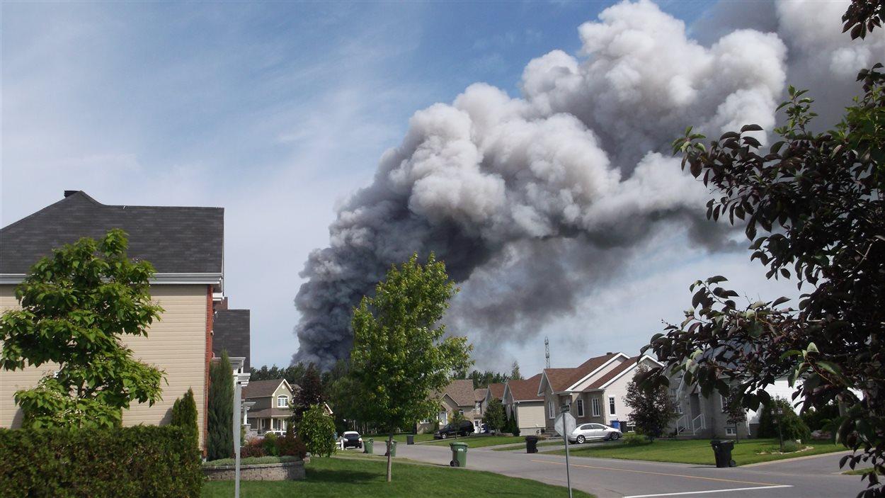 L'épaisse colonne de fumée monte dans le ciel de ce quartier résidentiel.