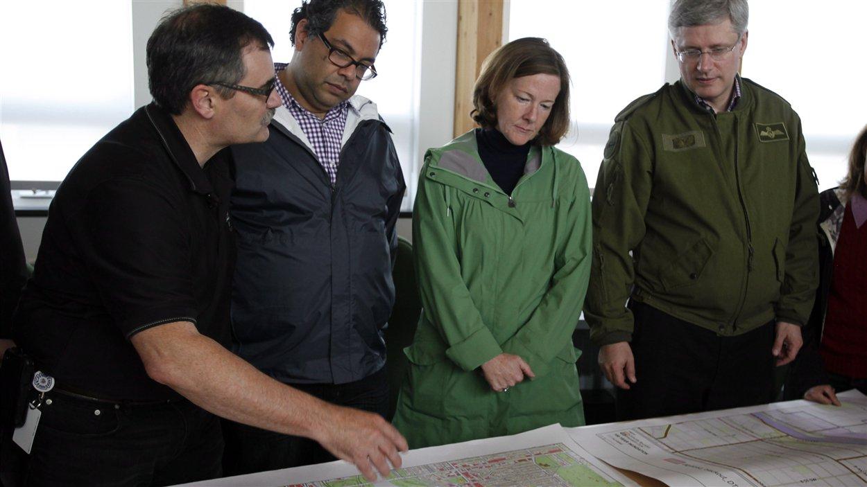 Le directeur de l'agence municipale de gestion des urgences, Bruce Burrell, montre à Stephen Harper, Alison Redford et Naheed Nenshi les zones touchées par les inondations, à Calgary.