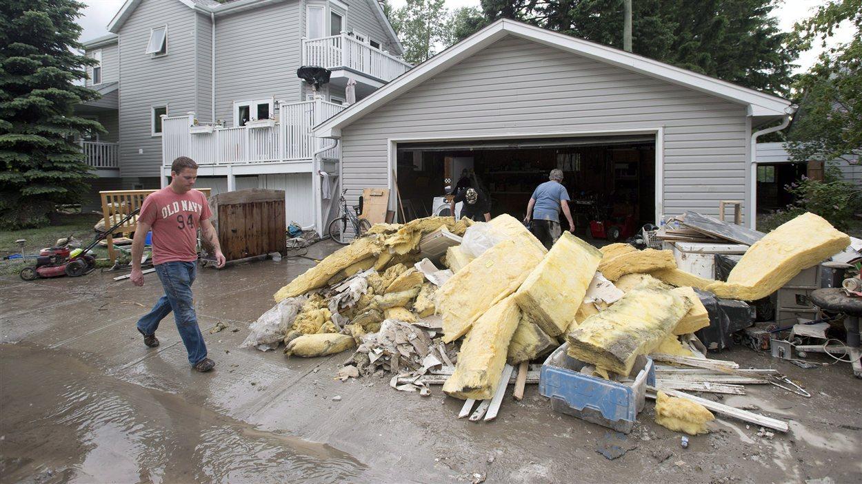 Des résidents du quartier Bowness à Calgary nettoient les dégâts causés par les inondations.